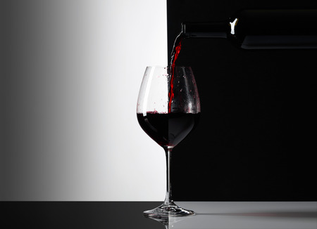 Red wine is poured into a glass. Reflexive background, copy space for your text.