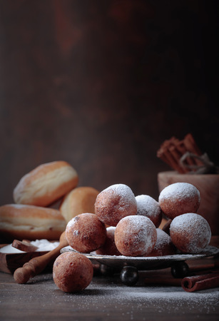 Sweet donuts with cinnamon sticks powdered with sugar on a old wooden table.
