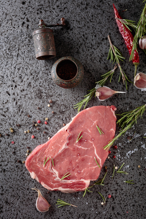 Raw beef steak with spices and herbs. Top view. Imagens