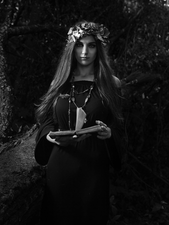 Beautiful young halloween witch wearing vintage gothic dress and holding magical book. Witch in dark forest. Black and white. Stockfoto