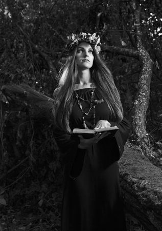 Beautiful young halloween witch wearing vintage gothic dress and holding magical book. Witch in dark forest. Black and white. Imagens - 110798465