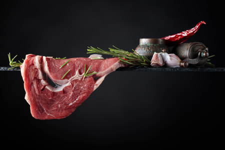 Raw beef steak with peppermill, garlic and rosemary. Black background, copy space.