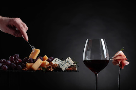 Glass of red wine with various cheeses , fruits and prosciutto on a black background. 写真素材