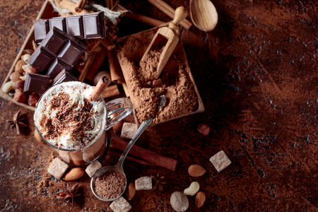 Cocoa with cream, cinnamon, chocolate pieces and various spices on a brown background. Top view, copy space for your text. Stock Photo