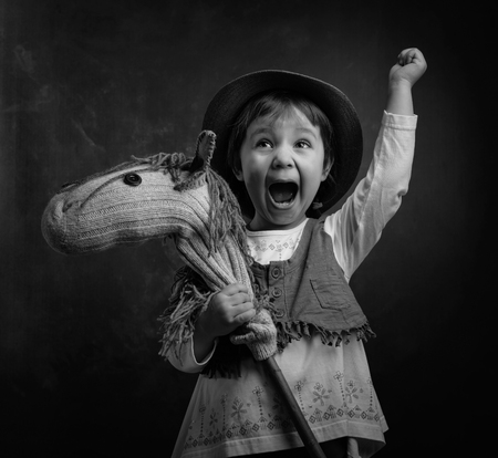 Screaming little girl with a homemade toy. Little girl dressed like a cowboy playing with a homemade horse. Expressive facial expressions. Black and white.
