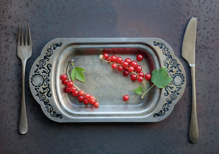 Redcurrants on a metal dish with fork and knife. Concept for healthy eating, dieting and antioxidant. Top view.