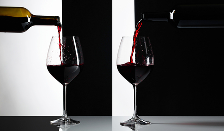 Red wine is poured into a glasses. Reflexive background, copy space for your text.