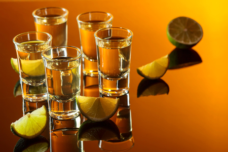 Small glasses of tequila and lime slices.