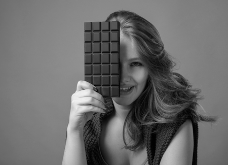 Happy young beautiful woman eating chocolate. Young blonde with natural makeup having fun and eating chocolate. Gray background, copy space. Black and white.
