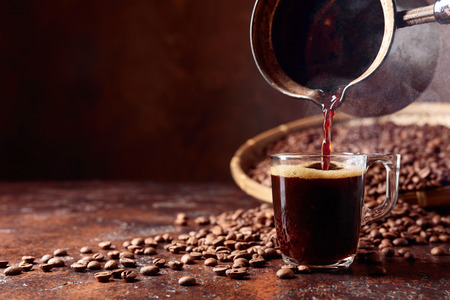 Black coffee is poured into a small glass cup from a old copper coffee maker. Copy space. Standard-Bild - 111913890