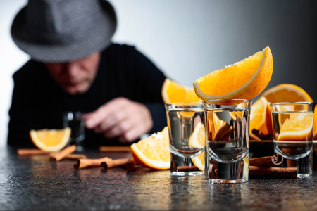 Glasses of tequila with orange and cinnamon sticks on a table in bar. Drinking man in a hat at the bar. Selective focus.