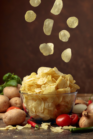 Potato chips with vegetables and spices on the kitchen table.