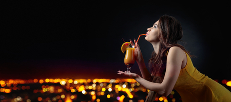 Young beautiful girl in a orange dress on a background of night city holding a glass of cocktail. Cocktail Tequila Sunrise garnished with cherry and slice of orange. Copy space.