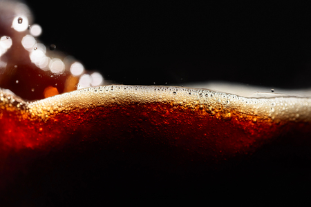 Close up of coffee splashes on a black background.