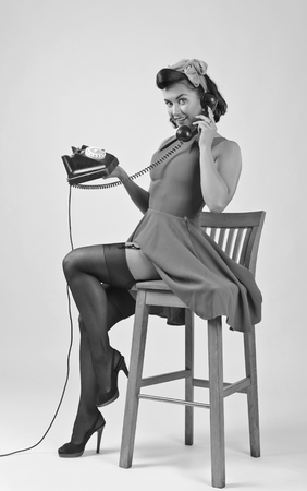Beautiful brunette woman in pin up style speaking via vintage phone. Attractive young woman in 50s style with perfect make-up and hairstyle. Black and white.