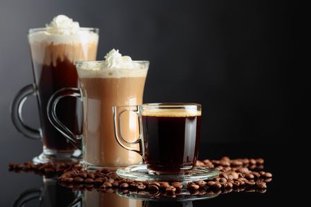 Various coffee drinks on black reflective background. Copy space.