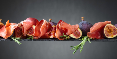 Prosciutto with figs and rosemary on a dark background.Copy space.