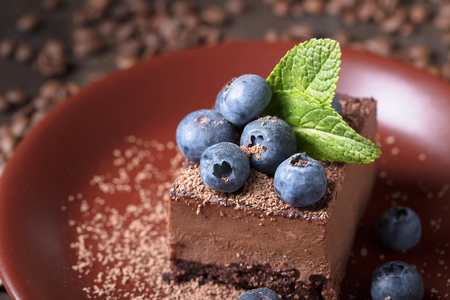 Chocolate cake with blueberries and mint on a brown plate. 写真素材