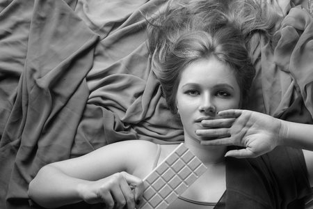 Happy young beautiful woman eating white chocolate. Young blonde with natural makeup having fun and eating chocolate. Top view.