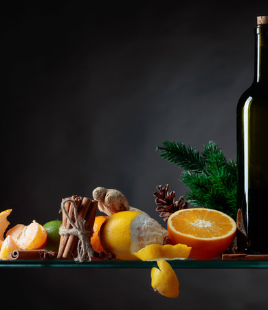 Ingredients for mulled wine hot drink with citrus and spices. Copy space for your content.