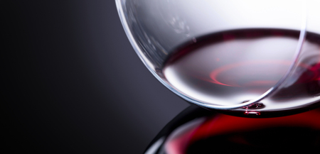 Glass of red wine, macro shot , black reflective background. Copy space for your text. Фото со стока