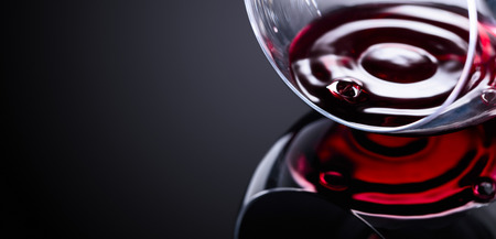 Glass of red wine, macro shot , black reflective background. Copy space for your text. 写真素材