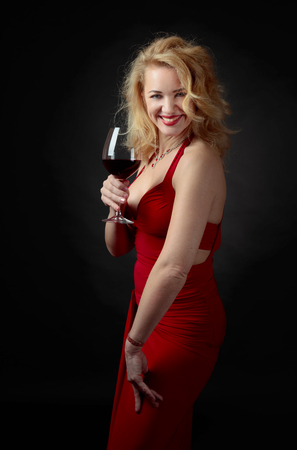 Attractive middle age woman in red evening dress with glass of red wine. Happy forty years blonde on a black background. Stock Photo