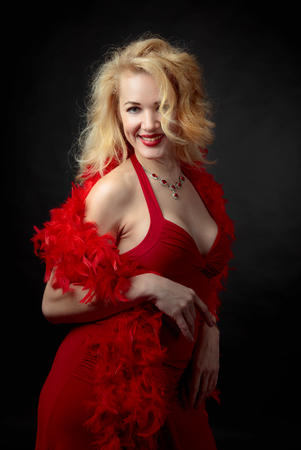 Attractive middle age woman in red evening dress with fluffy feather boa. Happy forty years blonde on a black background.