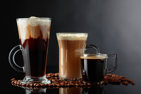 Various coffee drinks on black reflective background. Фото со стока