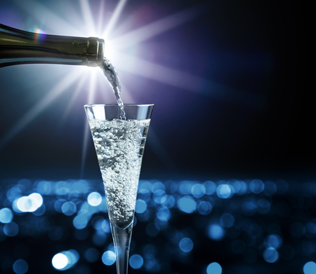 Champagne pouring into glass on a background of night city. Stream of wine being pouring into a glass close-up. Copy space. Stock fotó