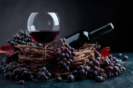 Bottle and glass of red wine with grapes.