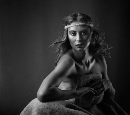 Portrait of young beautiful woman with curly hair and perfect makeup. Dress made of natural rough fabric, hippie style concept. Copy space for your content, black and white. Standard-Bild - 114609150