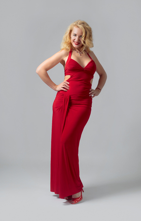 Attractive middle age woman in red evening dress. Happy forty years blonde on a white background.