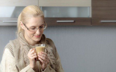 Close-up portrait of a beautiful mid age woman in glasses with cup of coffee. Attractive and happy blonde in sweater drinks latte. Copy space.