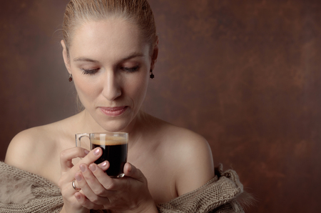 Close-up portrait of a beautiful mid age woman with cup of coffee. Attractive and happy blonde in sweater with bare shoulders drinks coffee. Copy space. Standard-Bild - 114996167