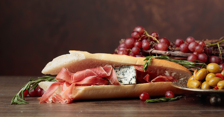 Sandwich with prosciutto, blue cheese and rosemary on a dark background. Delicious snack and grapes. Copy space for your text.