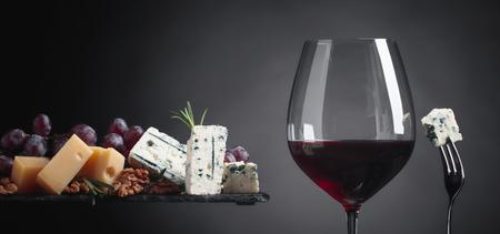 Glas rode wijn met verschillende kazen, druiven, walnoten en rozemarijn op een donkere achtergrond. Ruimte kopiëren. Stockfoto