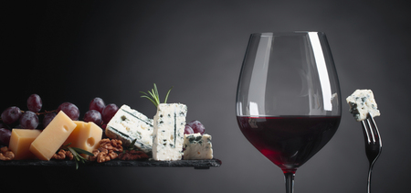 Glass of red wine with various cheeses, grapes, walnuts and rosemary on a dark background. Copy space .