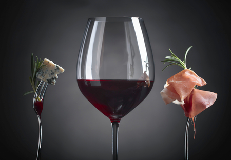 Glass of red wine with blue cheese, rosemary and prosciutto on a black background.