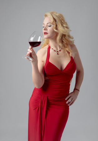 Attractive middle age woman in red evening dress with glass of red wine. Happy forty years blonde on a white background.