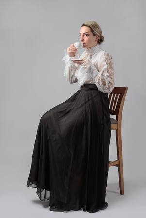 Portrait of a woman in Victorian clothes with a cup of coffee. White blouse with lace, embroidery and high collar. Long layered skirt with wide belt.