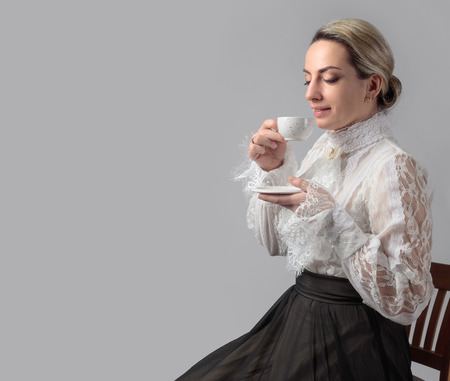 Portrait of a woman in Victorian clothes with a cup of coffee. White blouse with lace, embroidery and high collar. Copy space. Archivio Fotografico