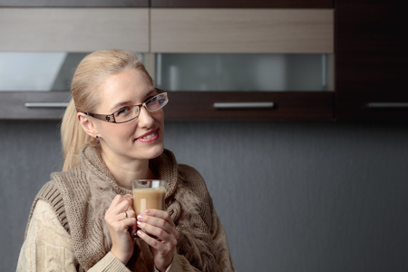 Portrait of a beautiful woman in glasses with cup of coffee. Attractive and happy blonde in sweater drinks latte. Copy space.