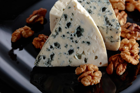 Soft blue cheese with walnuts on a black plate.