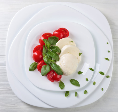 Mozzarella with tomato and green basil on a white plate . Healty organic food.