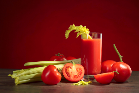Tomato juice with tomatoes and celery sticks on a wooden table. Copy space for your text.