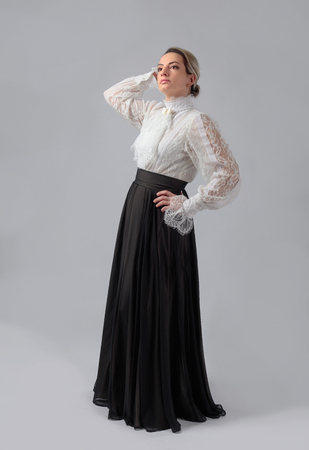 Portrait of a woman in Victorian clothes. White blouse with lace, embroidery and high collar. Long layered skirt with wide belt.