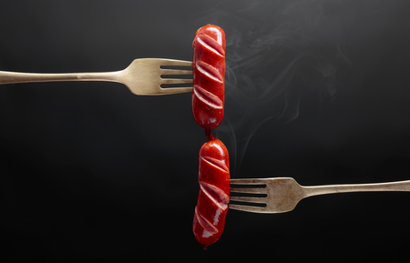 Grilled sausages on a forks. Black background, copy space.