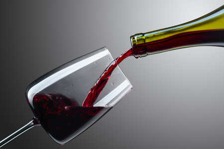Red wine being poured into glass  on a grey background. Saved clipping patch.