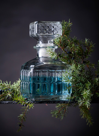 Gin in decanter and juniper branch with berries.